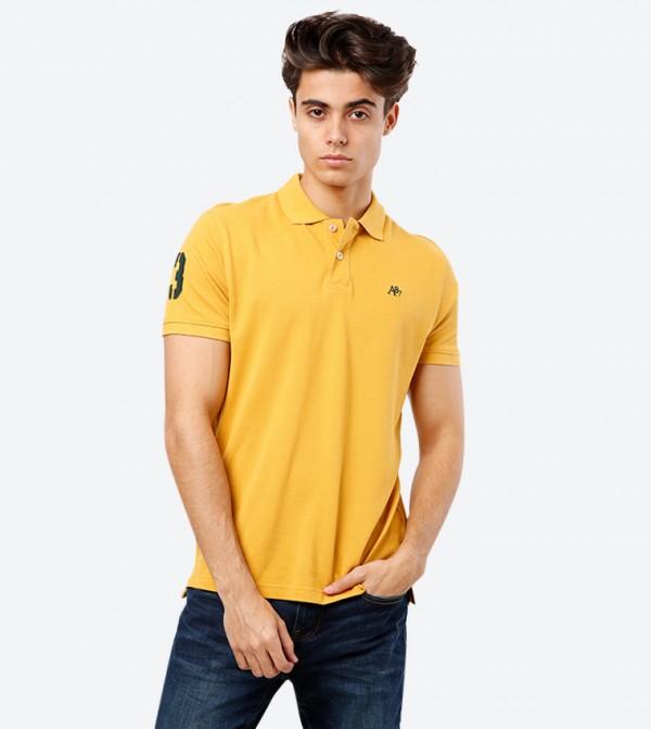 بلوز بولو مزيّن بالشعار مع ياقة كلاسيكية و أكمام قصيرة لون أصفر